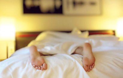 En person der ligger ned i en seng med sløret baggrund